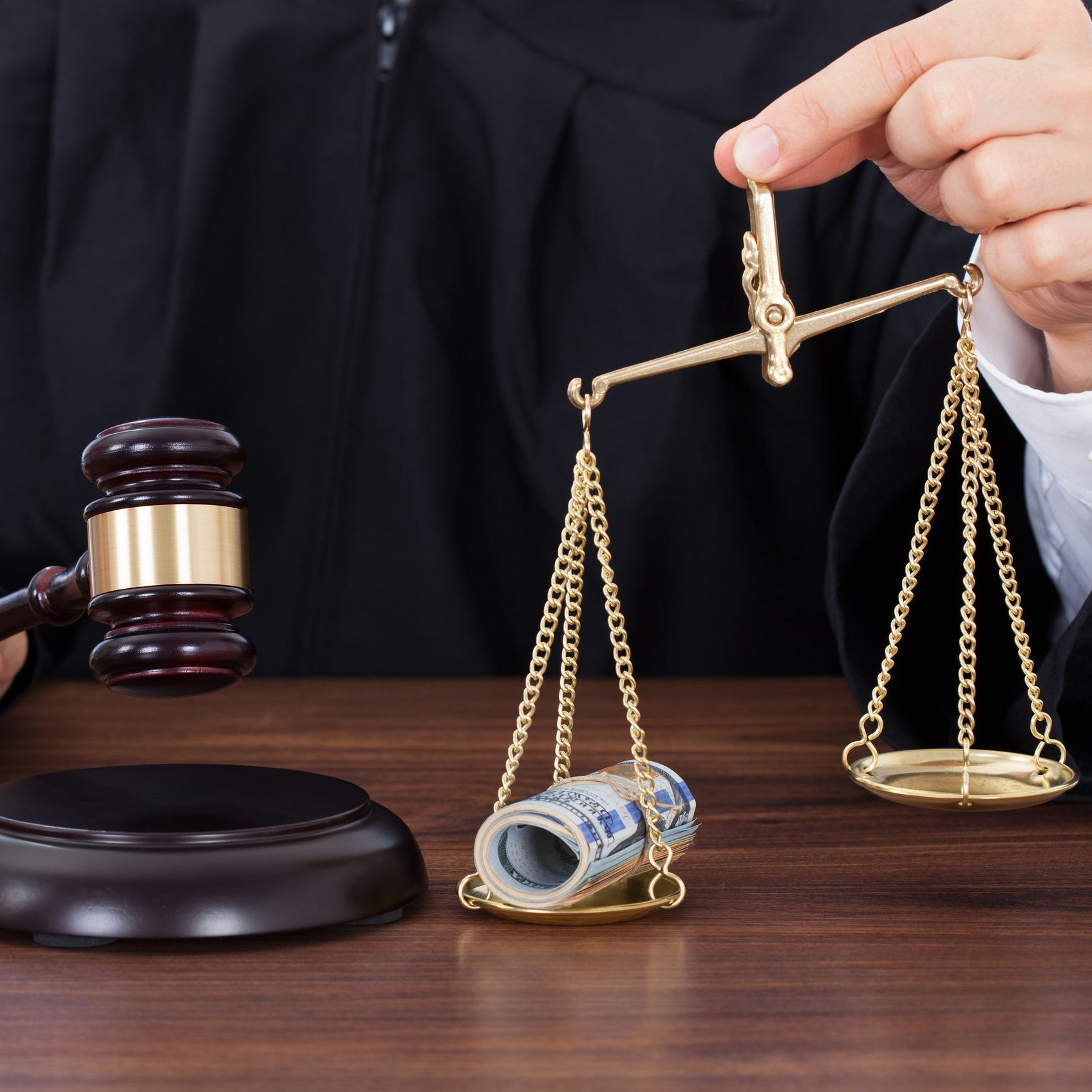 a judge holds a gavel and a set of scales with money in one side