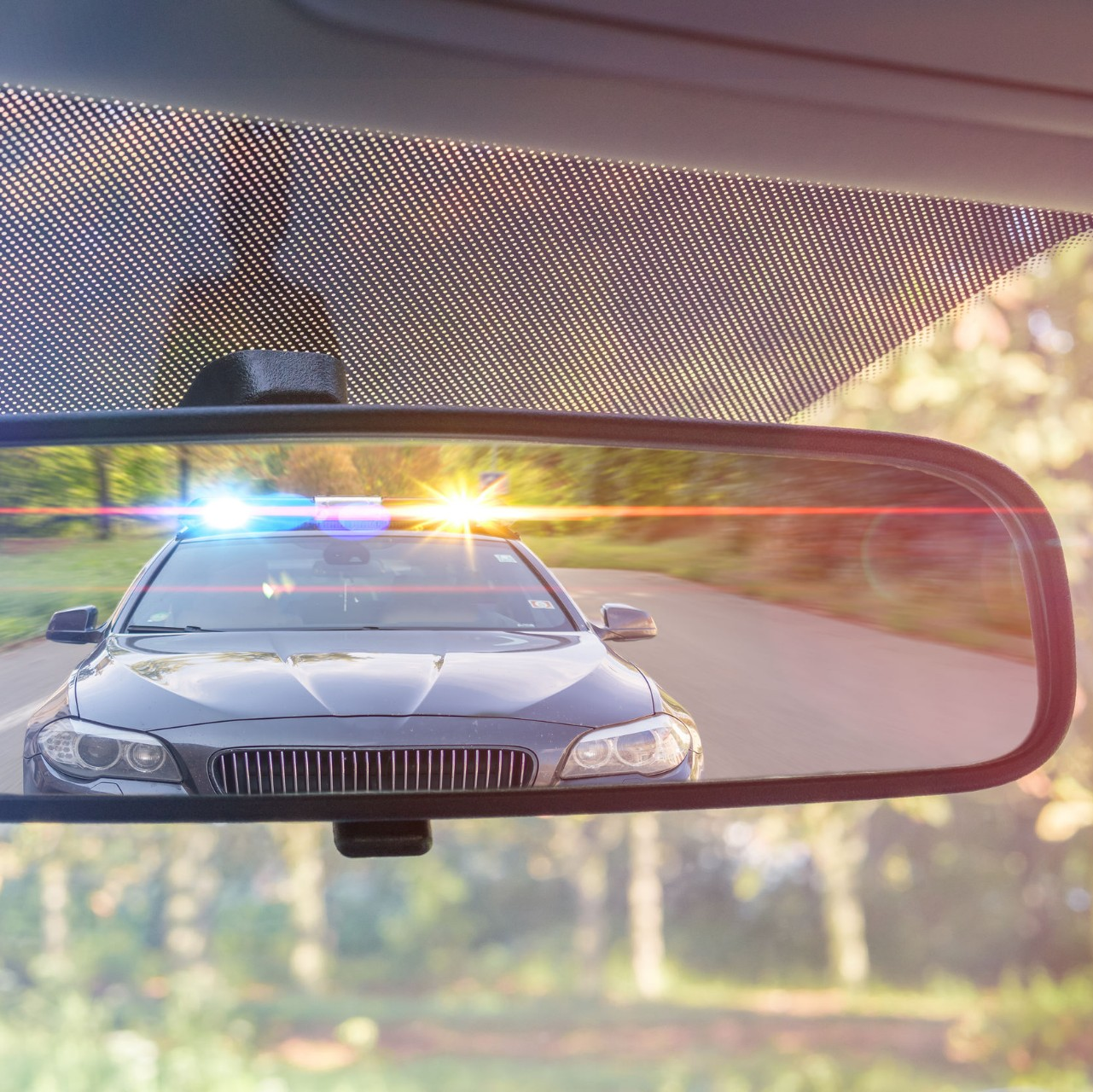 a police car is visible in a car's rear view mirror