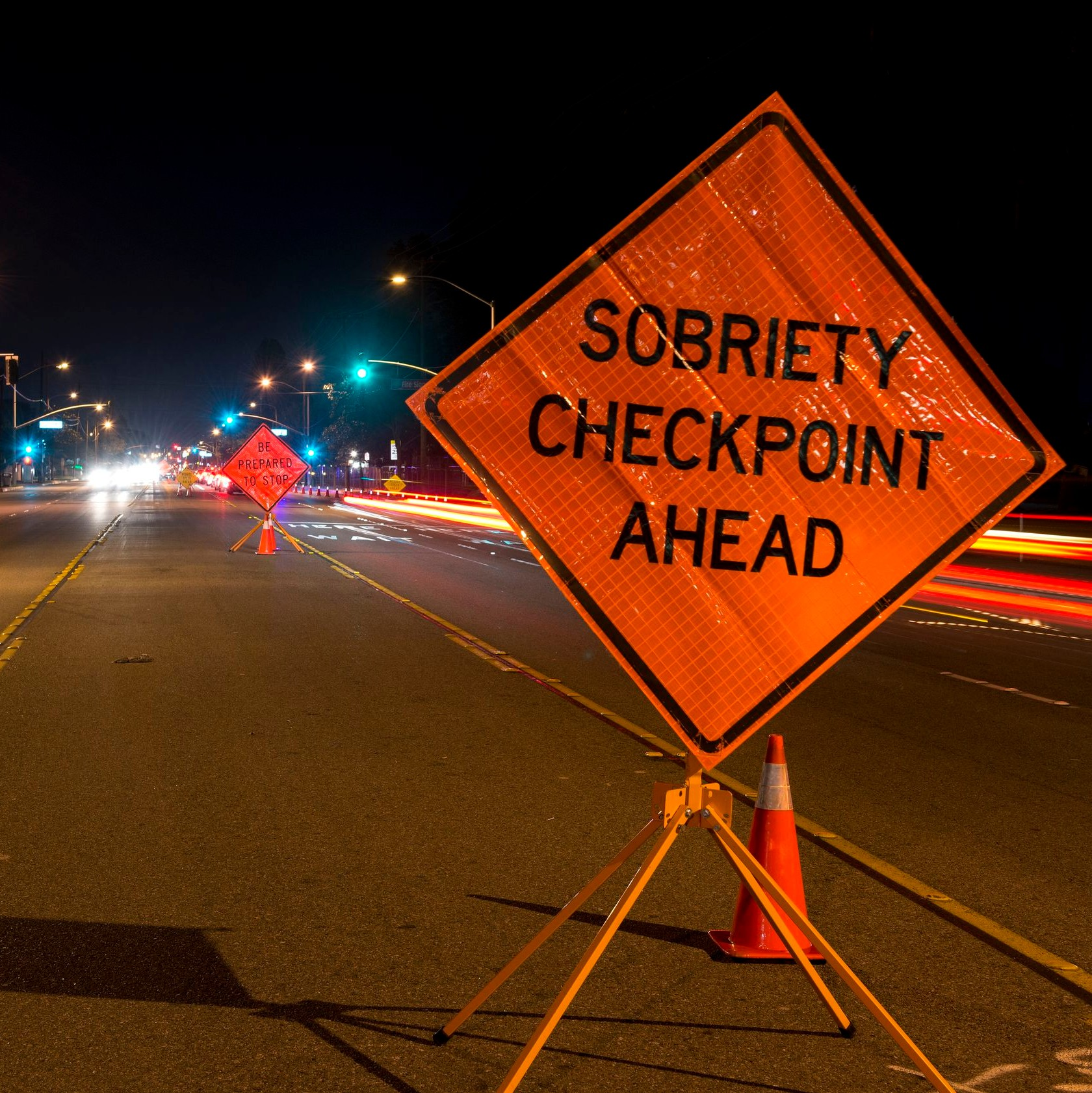 "an orange traffic sign rests on a road and reads ""sobriety checkpoint ahead"""