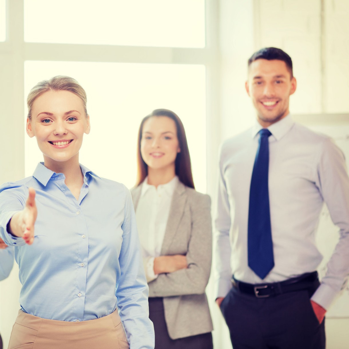 three business people smile and one extends her hand